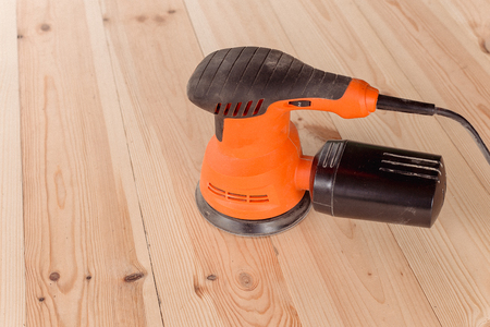 side view of the orbital sander on a wooden table