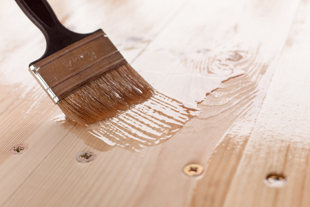 close-up of a mans hand varnishing a wooden table Stockfoto