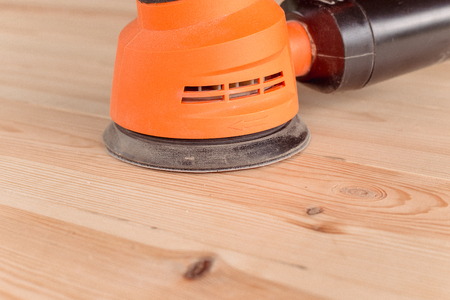 closeup of the orbital sander on a wooden table
