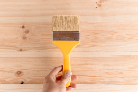 male hand holding a yellow paint brush on wooden background
