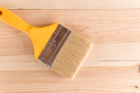 yellow paint brush on a wooden table