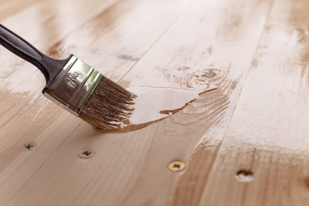 close-up of a mans hand varnishing a wooden table 写真素材