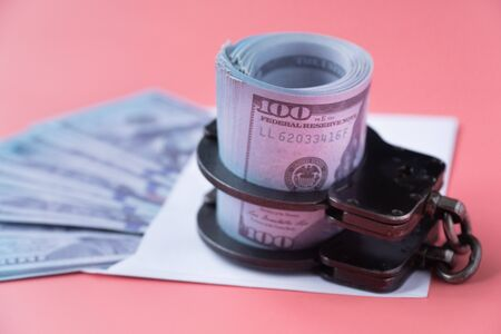 handcuffs on an envelope with money, pink background
