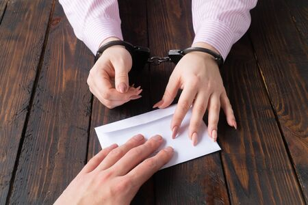 mens hands give money in envelope to womens hands in handcuffs against the background of a wooden table