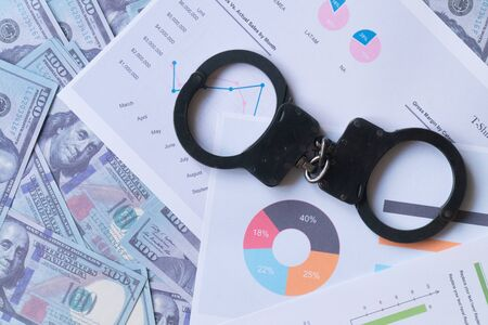 top view handcuffs against the background of charts and hundred-dollar bills Banque d'images