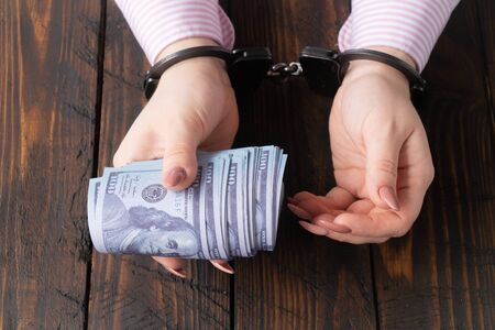 female hands in handcuffs hold twisted money on a dark wooden background