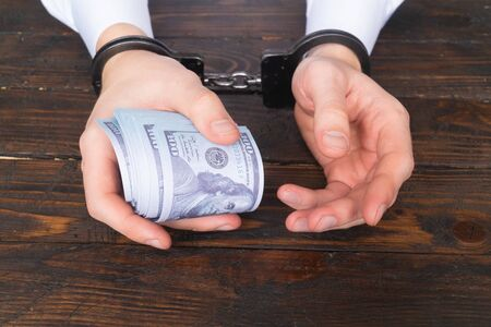 male hands in handcuffs hold twisted money on a dark wooden background Stock Photo