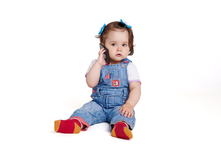lighthearted: Baby with mobile phone on a white background Stock Photo