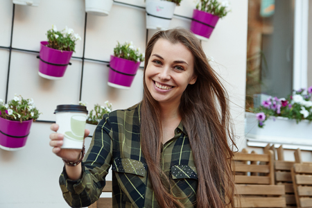 ady: smiling pretty girl sitting on bench with morning coffee