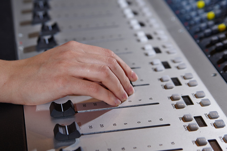 Closeup of hands  working on mixer console, twisting knobs, studio equipment concept Stock Photo