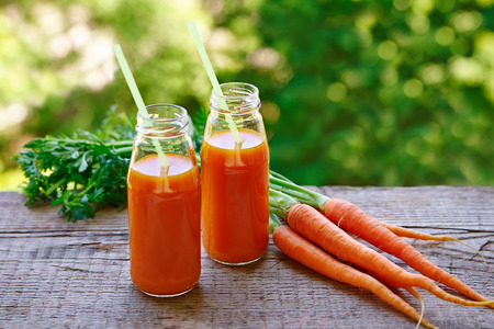 sun energy: Fresh carrot juice in glass bottles with straws, fresh carrots on a wooden table outdoors. Stock Photo