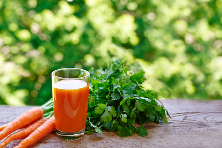 sun energy: Carrot juice in a glass and fresh carrots on a rustic wooden table