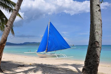 traditional paraw sailing boat on white beach on boracay island. philippines  Stock Photo