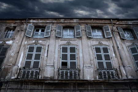 Old house with gray shutters and thunder clouds in the sky Stock Photo