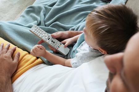 El padre y el niño están viendo la televisión juntos y cambiando el nuevo programa con un control remoto.