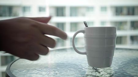 Close-up of a mans hand takes a mug of a hot drink from a table.