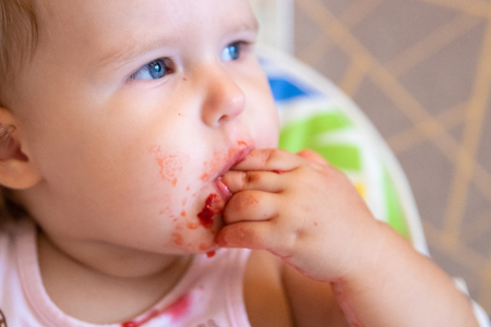 Cute little baby girl portrait funny eating red strawberries all smeared