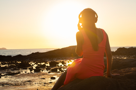 Girl in headphones listening to music in the city at sunset Imagens