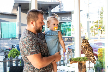 dad shows the baby an owl. baby strokes an owl. Standard-Bild