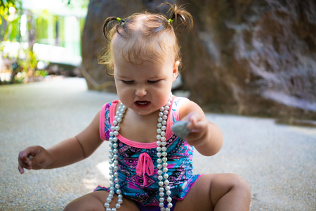 a girl in a bathing suit with white beads is surprised, rejoices, shouts, raises her hands. childrens fashion concept