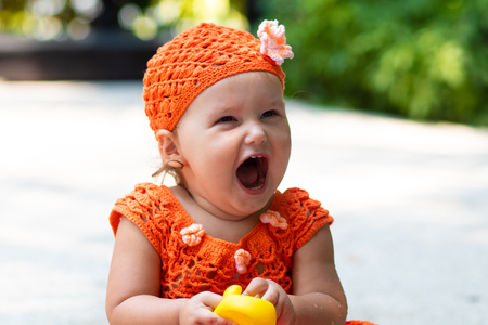 a girl in an orange knitted dress and hat is surprised, rejoices, screams, cries, raises her hands. childrens fashion concept
