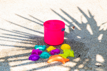 childrens beach bright pink toys on a sandy concrete background