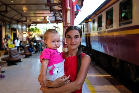 mother with baby is waiting for the train. Young mother travelling with baby by train