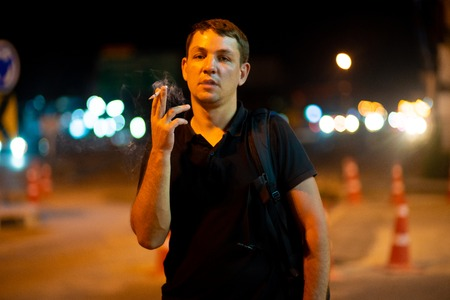 man smoking a cigarette on the street at night Zdjęcie Seryjne