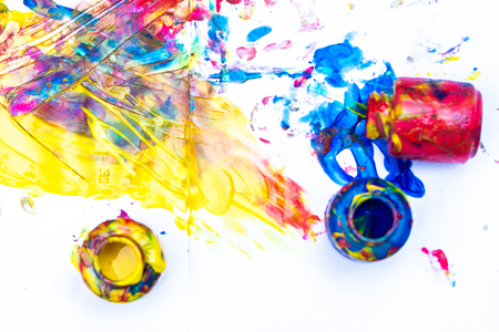 Finger paints - blue, red and yellow on a white sheet of paper. Creative child development in kindergarten or free time at home.