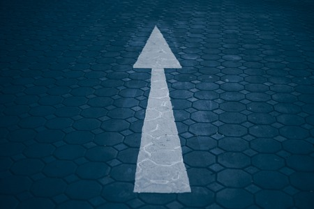 Asphalt road with an arrow up. Up arrow on gray background.