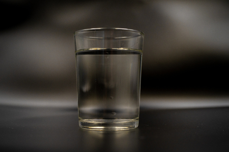 Just a glass of water on a dark wooden table. Mineral water in a glass on a black background. A glass with water.