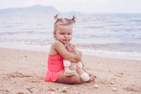 pensive little girl hugging teddy bear and looking away while sitting on seashore