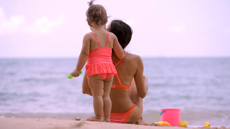 mom and daughter in pink swimsuits on the shore of a beautiful beach playing in the sand with childrens beach toys. Mom and child look into the distance on the blue sea. concept of motherhood Stockfoto