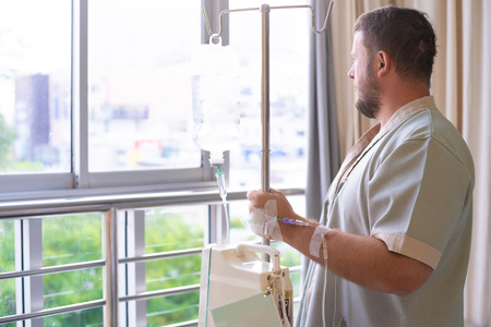 patient with a dropper looks out the window of the hospital room and smiles. back view. Healthcare concept