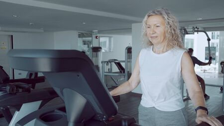 Senior woman is engaged on a treadmill in the gym against Redactioneel