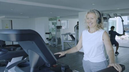 senior woman is engaged on a treadmill in the gym. blond female listens to music with headphones on the treadmill.