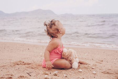 pensive little girl hugging teddy bear and looking away while sitting on seashore Фото со стока