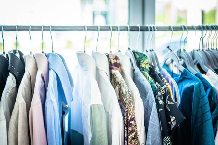 Summer wardrobe showcase. White and gray tone knitwear hanging on a coat rack. Selective focus, horizontal. Stock Photo