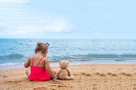 Cute girl near the sea. Young girl with teddy bear sitting on the beach