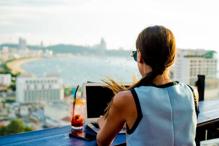 female works on a laptop in a cafe on the roof of a high-rise with a beautiful panoramic view of the city, close up.