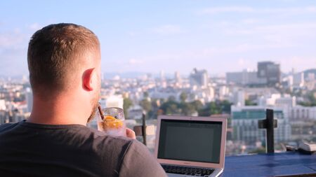 male working on a laptop in a cafe on the roof with a beautiful panoramic view. man drinking a cocktail and working on a computer
