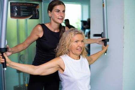 Pattaya, Thailand - May 15, 2019: Senior woman is engaged on a simulator in the gym with a personal trainer. daughter helps mom in the gym. Redactioneel