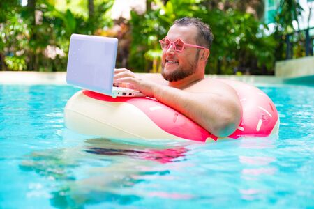 Fat funny man in pink inflatable circle in pink glasses works on a laptop in a swimming pool.