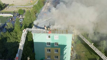 Nizhnevartovsk, Russia - July 1, 2019: firefighters extinguish a fire on the roof of a residential highrise building. top view.