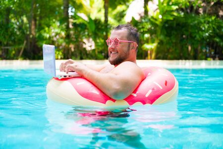 smiling Fat funny man in pink inflatable circle in pink glasses works on a laptop in a swimming pool.