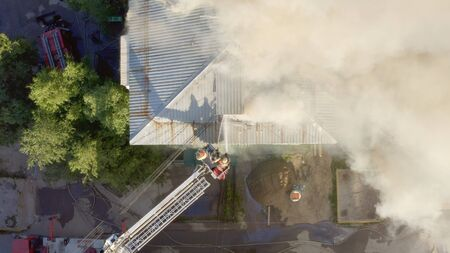 Brennendes Dach eines Wohnhochhauses, Rauchwolken vom Feuer. Feuerwehrleute löschen das Feuer. Ansicht von oben.