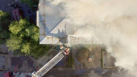 Techo en llamas de un edificio residencial de gran altura, nubes de humo del fuego. los bomberos apagan el fuego. vista superior.