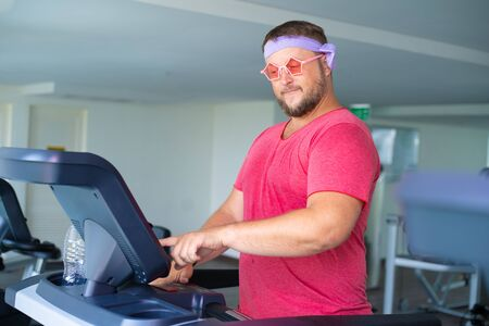 Funny fat male in pink glasses and in a pink t-shirt is engaged on a treadmill in the gym depicting a girl. man presses a button on a treadmill. Banque d'images