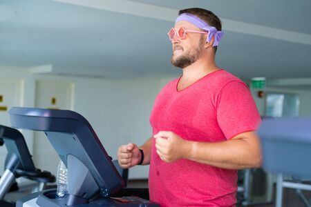 Funny fat male in pink glasses and in a pink t-shirt is engaged on a treadmill in the gym depicting a girl.