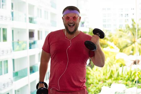Funny fat male in pink glasses and in a pink T-shirt engaged with dumbbells in the gym portraying a girl.